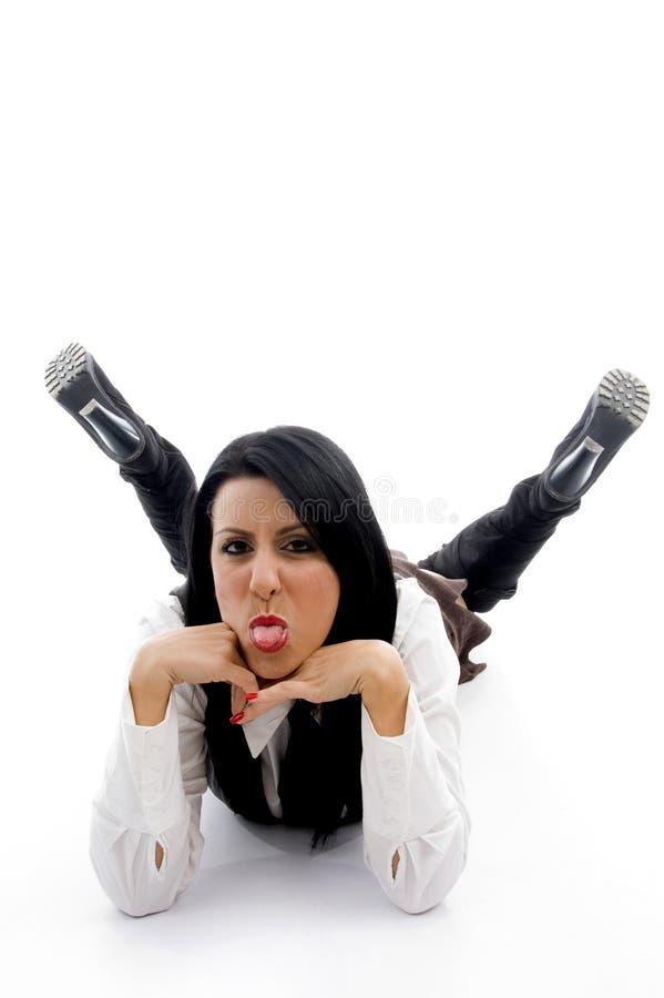 Mulher nova que encontra-se para baixo no assoalho e que arrelia fotografia de stock royalty free