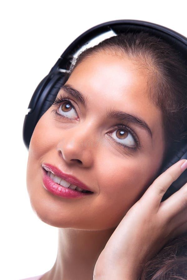 Mulher nova que escuta a música através dos auscultadores. fotos de stock royalty free