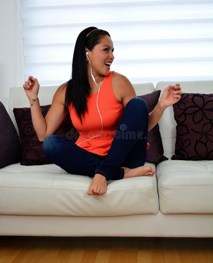 Mulher nova que escuta a música em casa imagem de stock royalty free