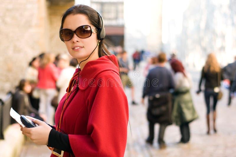 Mulher nova que escuta o guia audio imagens de stock royalty free