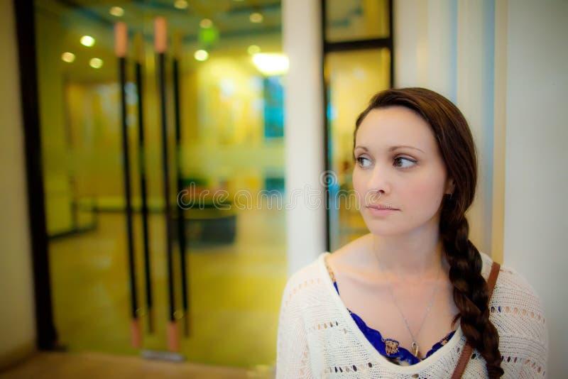 Mulher nova que espera na frente da porta do hotel em Ásia fotos de stock royalty free