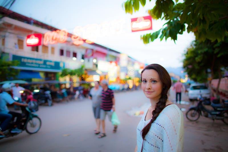 Mulher nova que espera para cruzar a estrada em Ásia imagens de stock royalty free