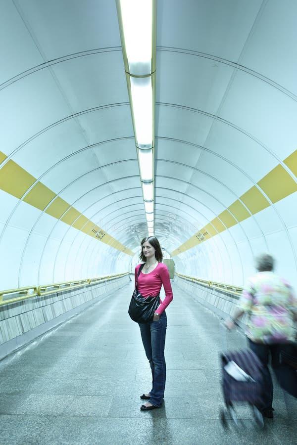 Mulher nova que está em um corredor do metro imagens de stock royalty free