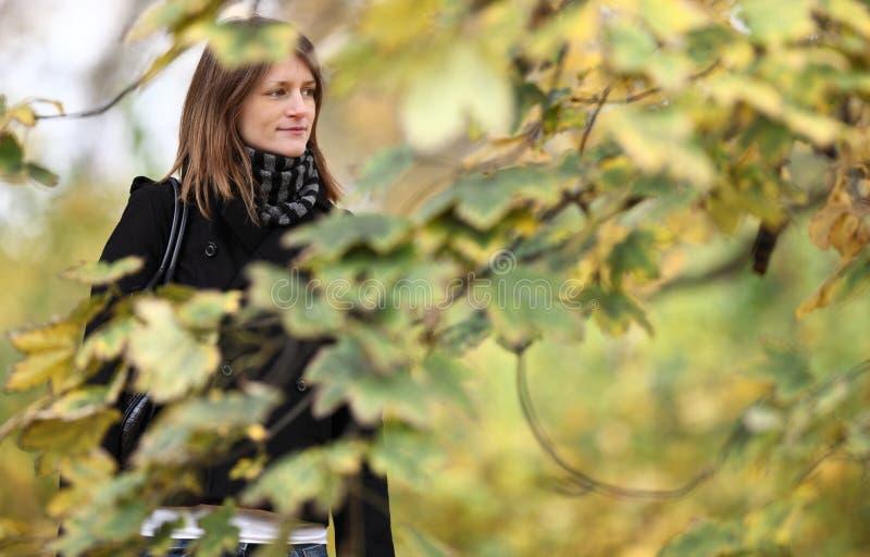 mulher nova que está em um parque imagem de stock royalty free