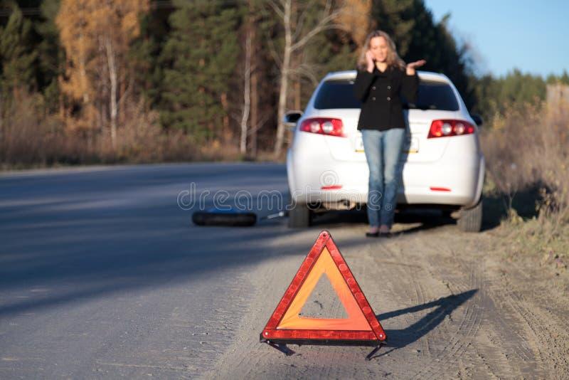 Mulher nova que está por seu carro danificado imagem de stock