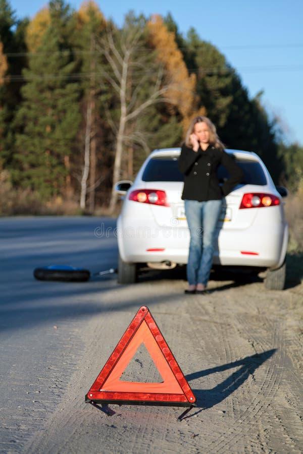 Mulher nova que está por seu carro danificado imagem de stock royalty free