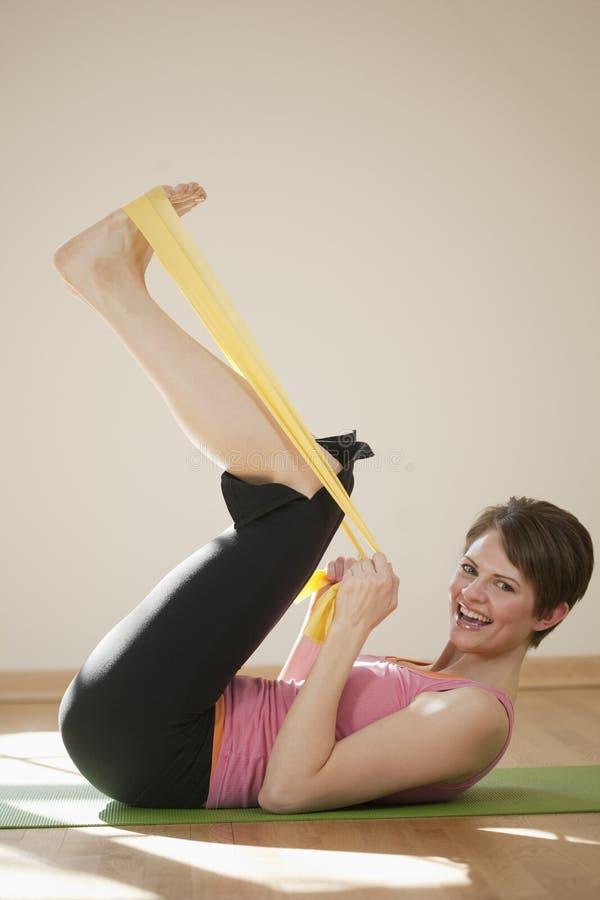 Mulher nova que exercita com faixas da resistência fotos de stock royalty free