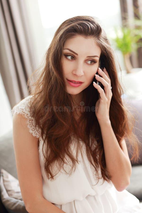 Mulher nova que fala no telemóvel imagens de stock