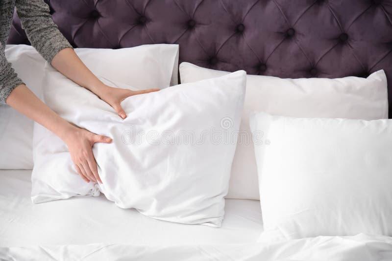 Mulher nova que faz a cama imagem de stock