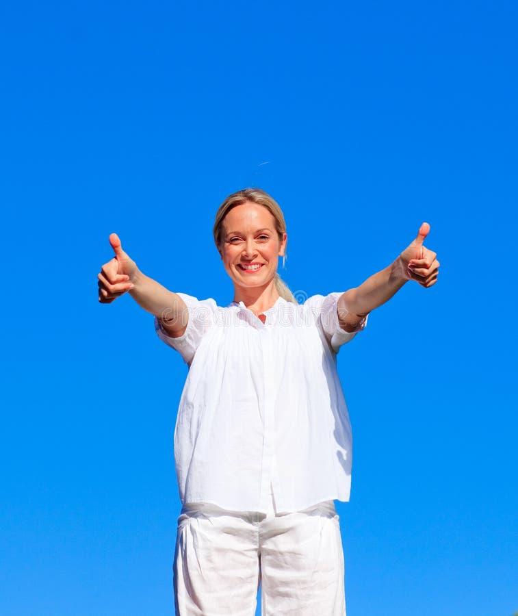 Mulher nova que faz exercícios com polegares acima fotografia de stock royalty free