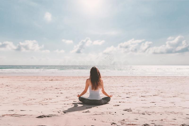 Mulher nova que faz a ioga na praia imagens de stock