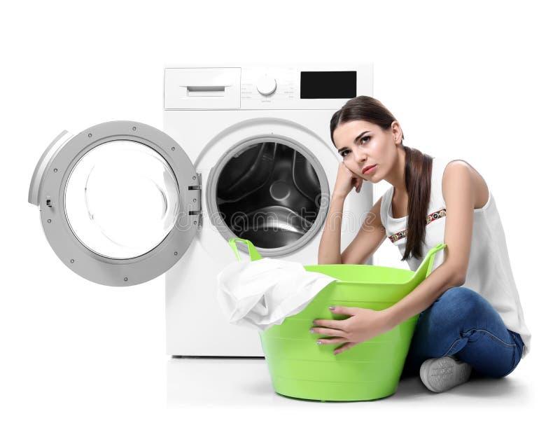 Mulher nova que faz a lavanderia imagem de stock