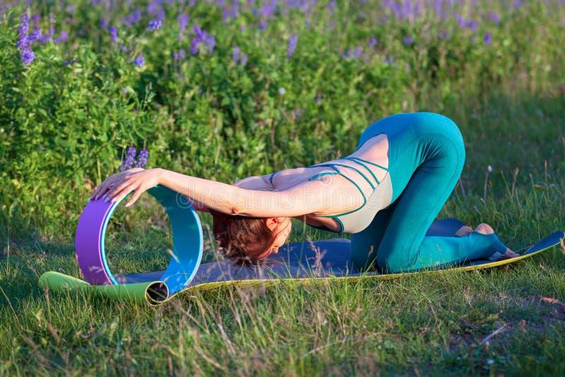 Mulher nova que faz o exerc?cio da ioga ao ar livre fotos de stock royalty free