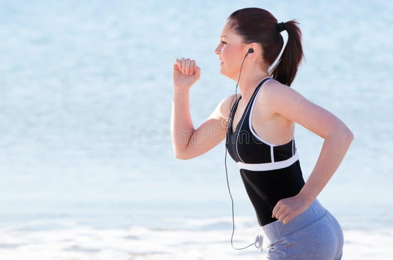 Mulher nova que funciona e que escuta a música foto de stock royalty free