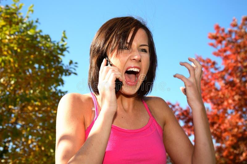 Mulher nova que grita no telefone foto de stock