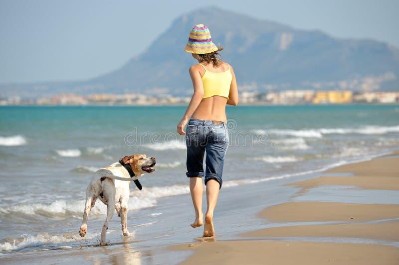 Mulher nova que joga com seu cão na praia imagens de stock