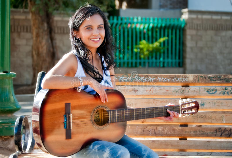 Mulher nova que joga a guitarra em um parque fotos de stock royalty free