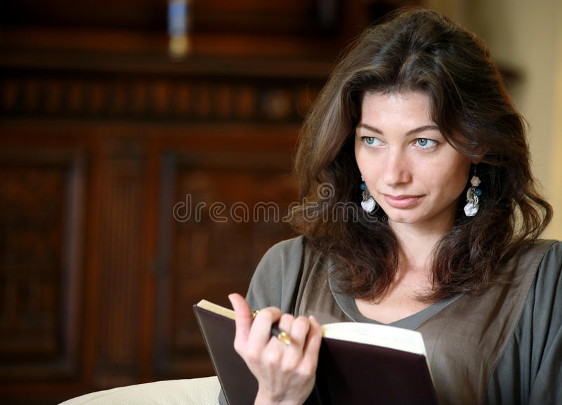 Mulher nova que lê um livro foto de stock royalty free