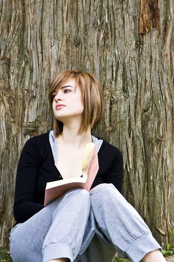 Mulher nova que lê um livro fotos de stock