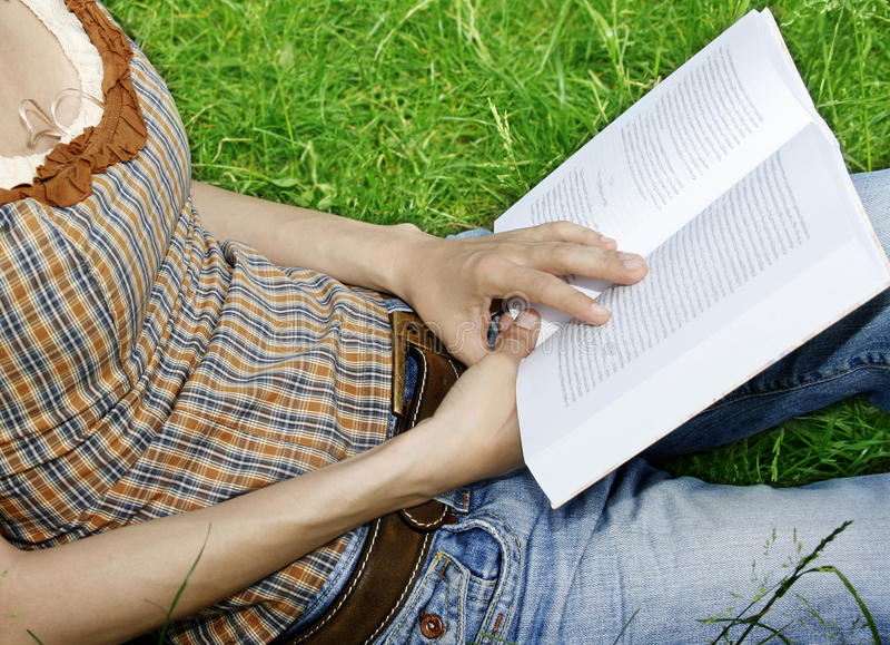 Mulher nova que lê uma novela fotos de stock royalty free