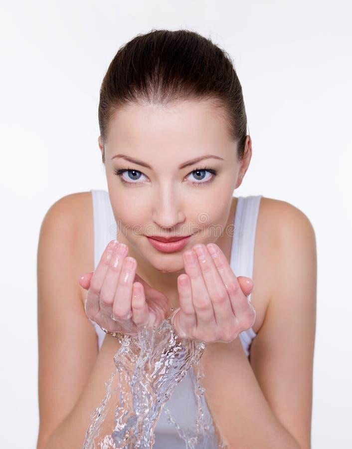 Mulher nova que lava sua face com água fotos de stock
