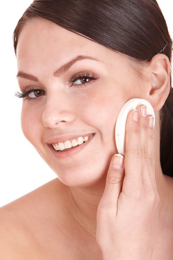 Mulher nova que lava sua face pela esponja. imagens de stock