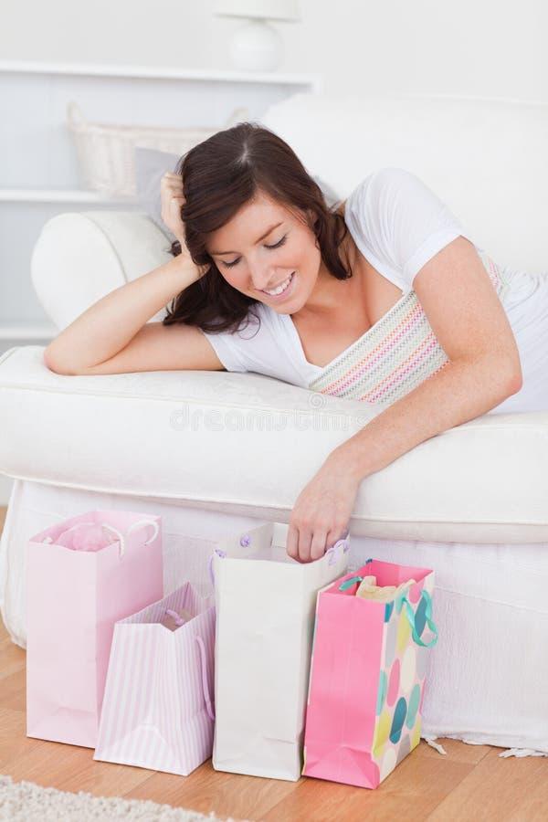 Mulher nova que levanta com seus sacos de compra foto de stock royalty free