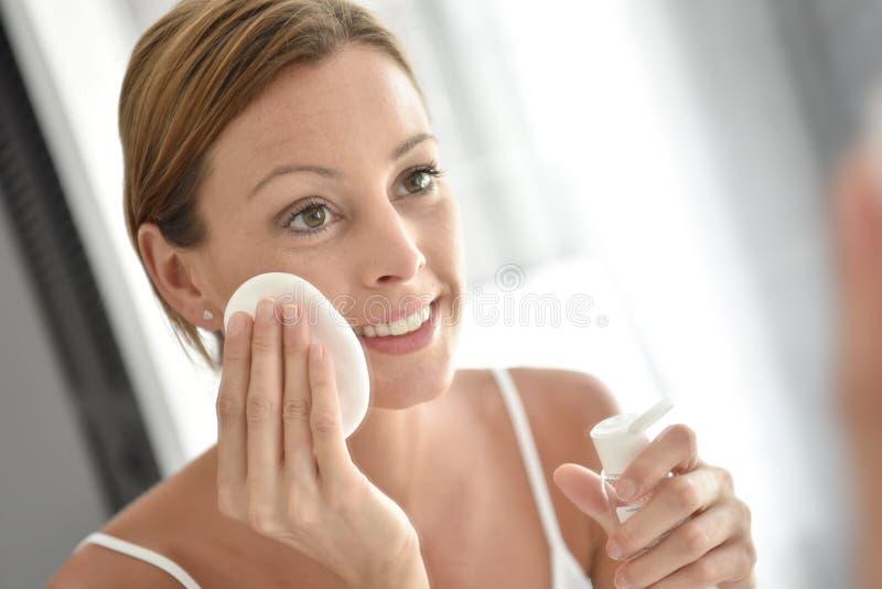 Mulher nova que limpa sua face foto de stock royalty free