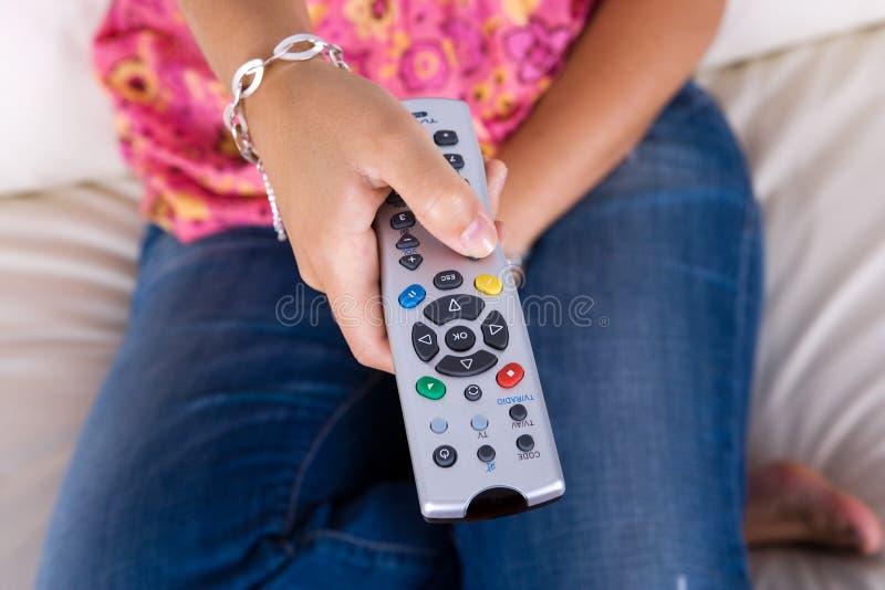 Mulher nova que mantem a televisão de controle remoto imagens de stock