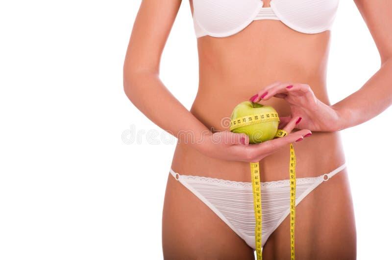 Mulher nova que mede sua cintura imagens de stock