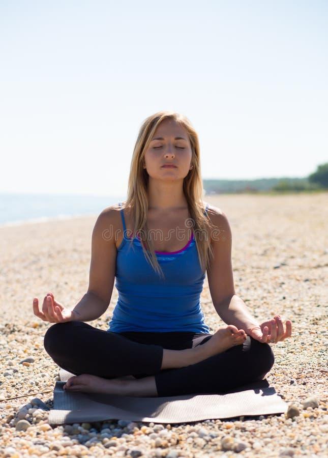 Mulher nova que meditating na praia imagem de stock royalty free