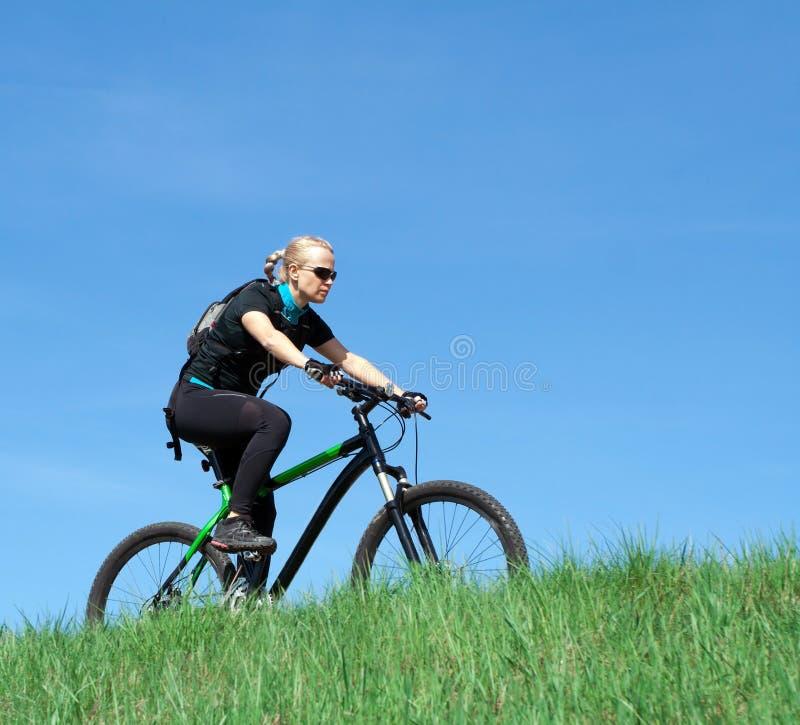 Mulher nova que monta uma bicicleta de montanha fotos de stock royalty free