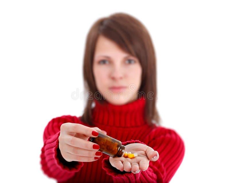Mulher nova que mostra comprimidos foto de stock