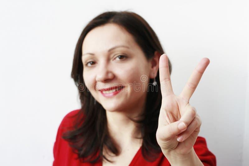 Mulher nova que mostra o símbolo da paz imagem de stock royalty free