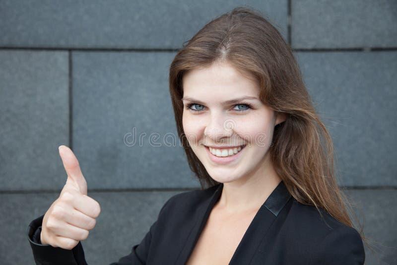 Mulher nova que mostra os polegares acima fotografia de stock