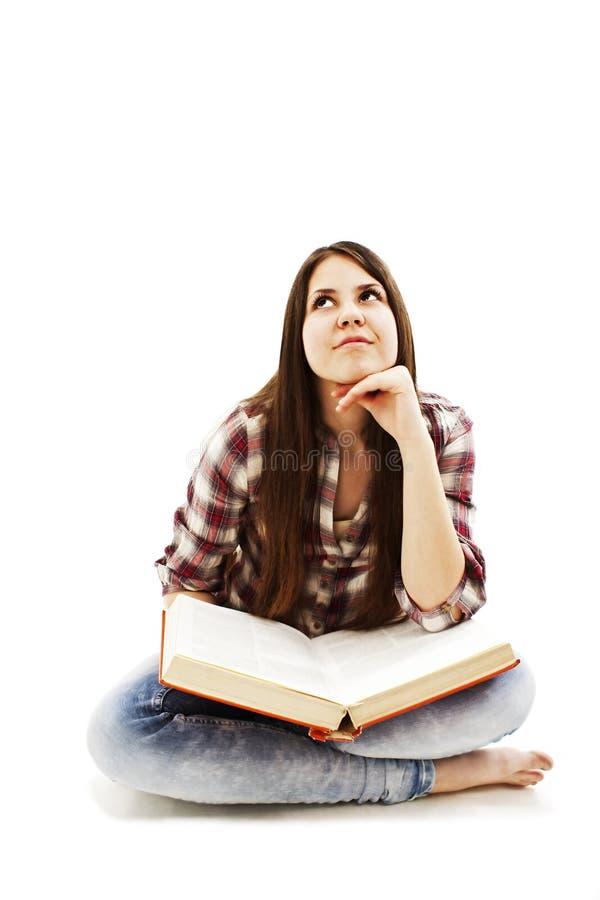 Mulher nova que olha acima ao ler um livro foto de stock
