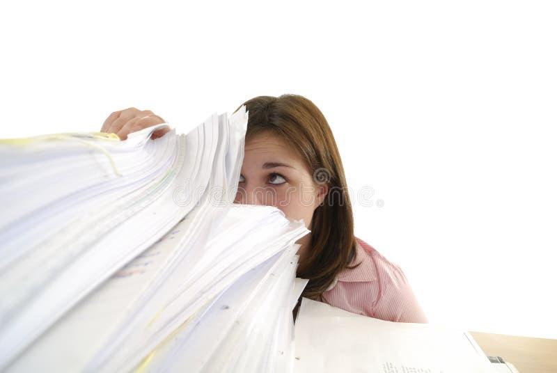 Mulher nova que olha em uma pilha de papéis fotos de stock