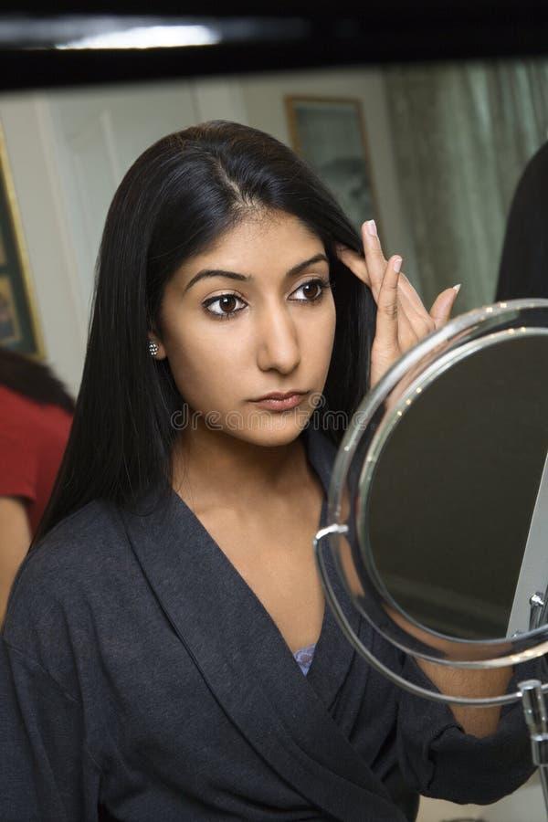 Mulher nova que olha no espelho. foto de stock royalty free
