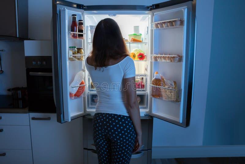 Mulher nova que olha no refrigerador fotos de stock royalty free