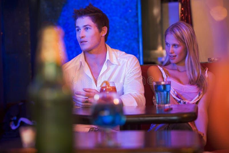 Mulher nova que olha um homem novo em um clube nocturno imagem de stock