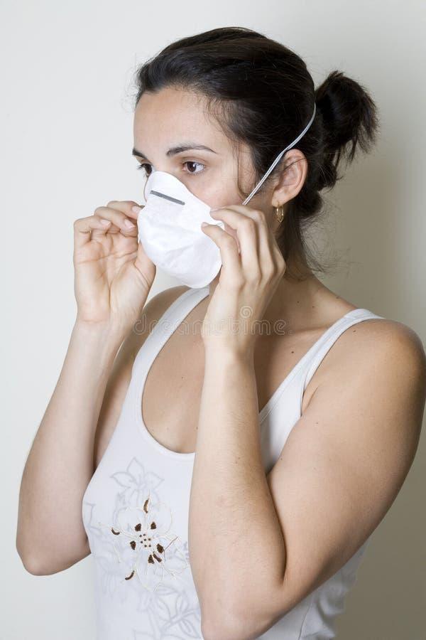Mulher nova que põr sobre uma máscara de encontro à gripe dos suínos imagem de stock