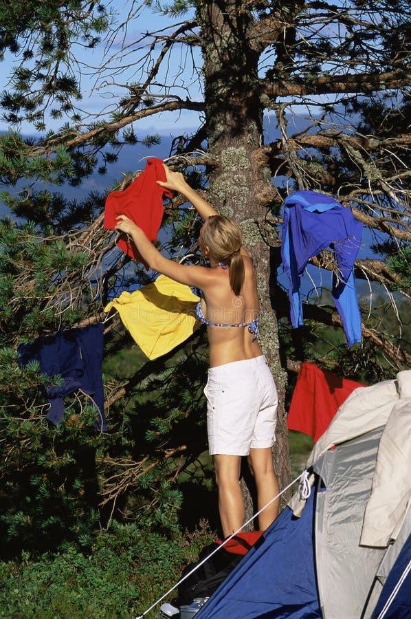 Mulher nova que pendura para fora o lavagem em uma árvore imagens de stock