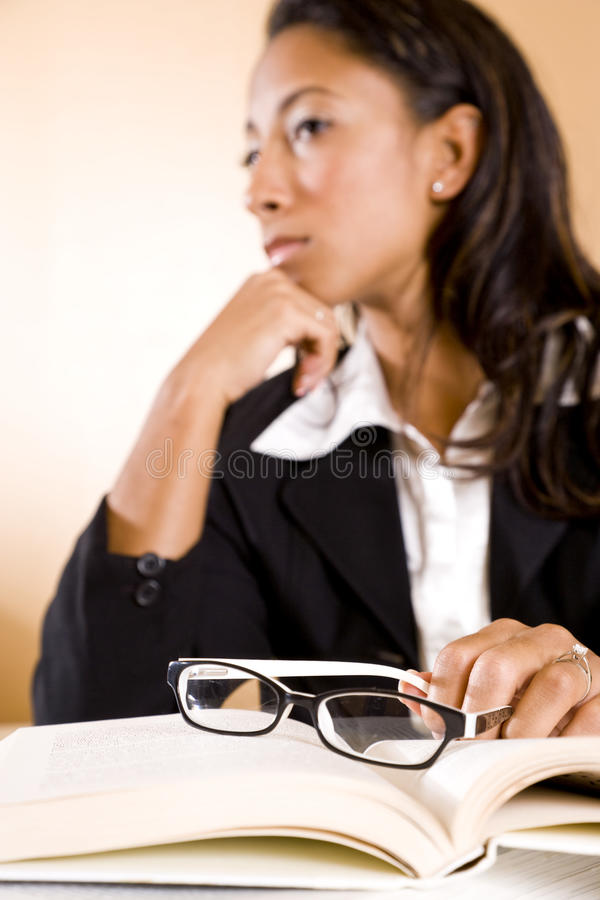 Mulher nova que pensa, foco em eyeglasses no livro foto de stock royalty free