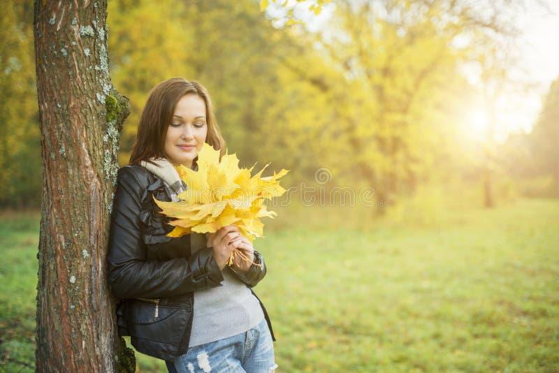 Mulher nova que prende a folha amarela fotos de stock