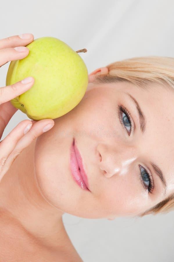 Mulher nova que prende a maçã verde imagens de stock royalty free