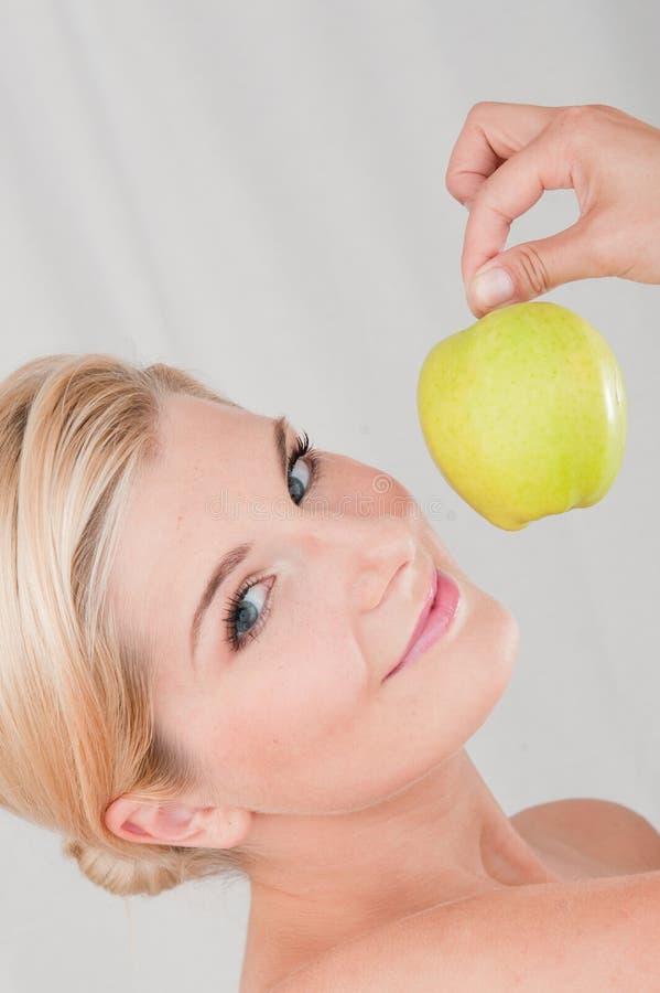 Mulher nova que prende a maçã verde foto de stock royalty free