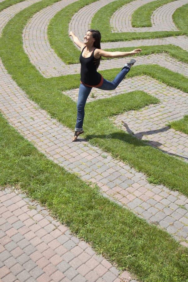 Mulher nova que pula sobre um labirinto da grama fotos de stock royalty free
