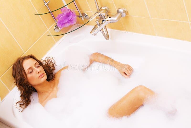 Mulher nova que relaxa em um banho fotos de stock