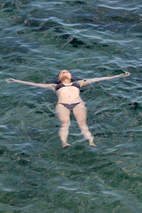 Mulher nova que relaxa no mar foto de stock