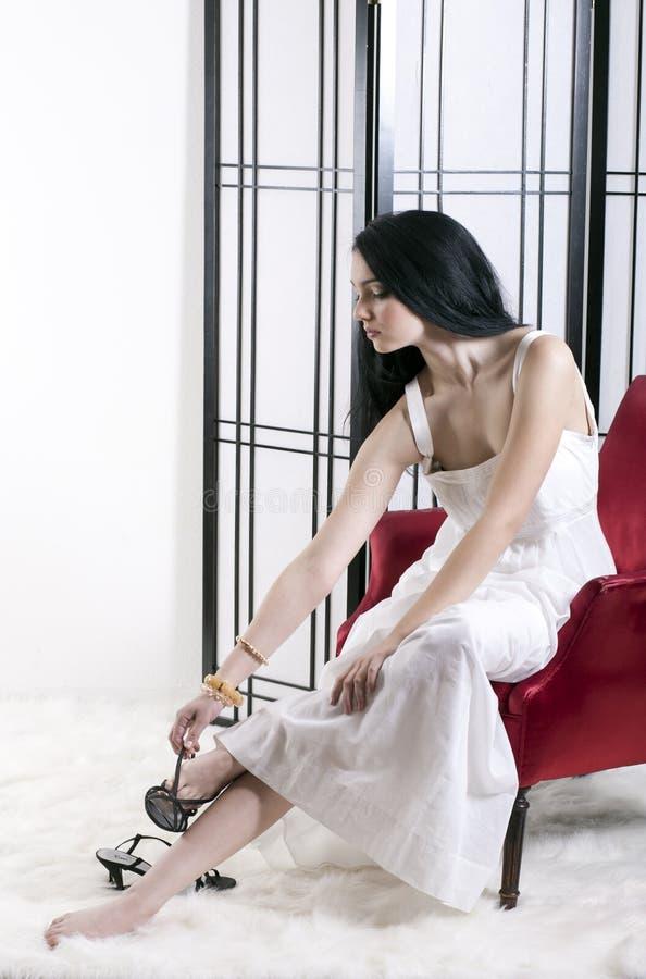 Mulher nova que remove as sapatas fotos de stock